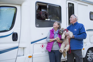 Family and dogs playing next to motorhome