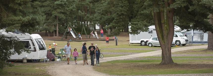 family walking on sandringham campsite with play area in the background