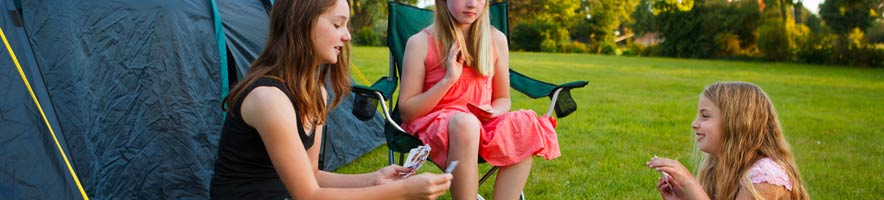 Girls playing cards on a campsite (shutterstock, Ramona Heim)