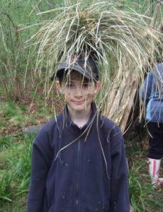 Learning to build a den is a great activity to enjoy when camping, as shown by a young Tom McGrath