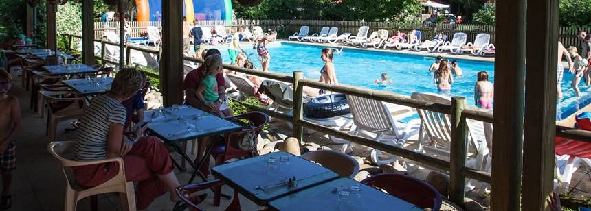 Bar terrace and pools at Camping Le Vaubarlet, Auvergne