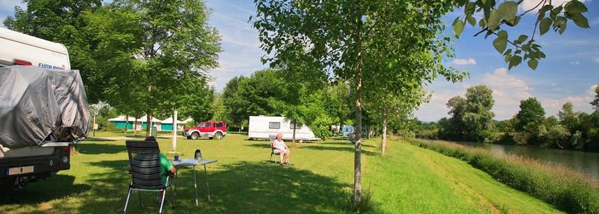 Pitches by the river at Camping la Plage Blanche, Ounans, France
