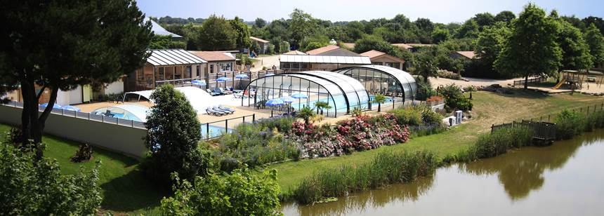 A view over the fishing lake to pool terrace at Camping La Bretonnière, Vendée, France