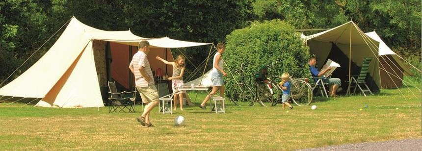 Families Relaxing On Grass Pitches at the La Ferme Du Latois Campsite, France