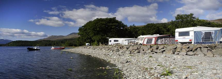 Caravans and tents pitched by the lake at Cashel Campsite