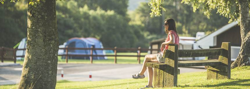 Woman relaxing on a bench at Bracelands Campsite, Forest of Dean