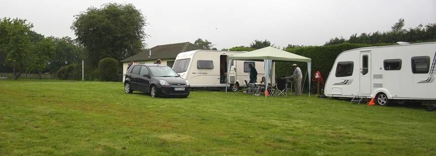 Caravanners enjoying the graasy site at Gosfield Lawn Tennis Club site.