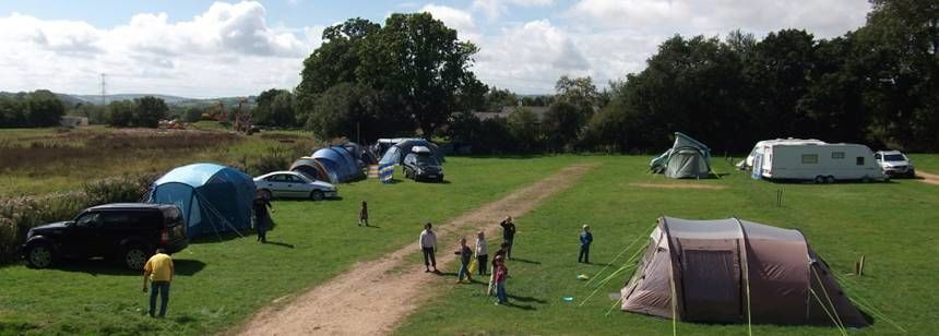 Aerial view of people at Diggerland Campsite with caravans and tents in field