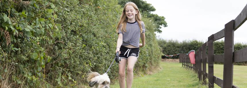 Girl walking dog on Bude Campsite