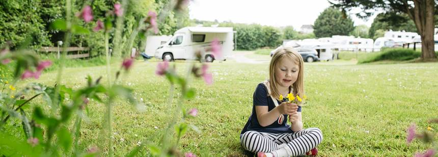 Girl playing with flowers on California Cross Campsite