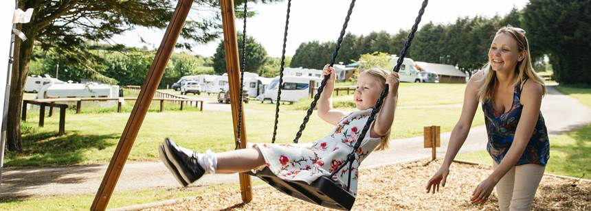 Woman pushing child on swing in California Cross Campsites play area