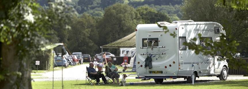 A Couple With Their dog Relaxing in the Shade of the Rhandirmwyn Camp Site. Carmarthenshire