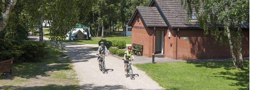 A Couple Cycling Through the Picturesque Surrounds of the Woodhall Spa Camp Site, Lincolnshire