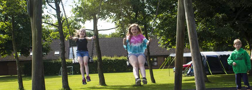 Kids playing on swings at Blackmore Club Site