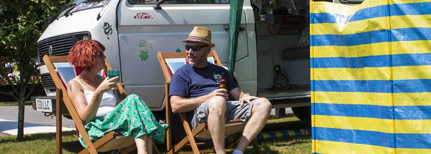 Couple relaxing outside capervan on Canterbury Camping and Caravanning Club Site