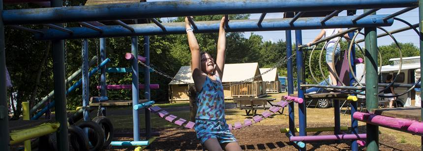 Girl playing on monkey bars at Canterbury Camping and Caravanning Club Site