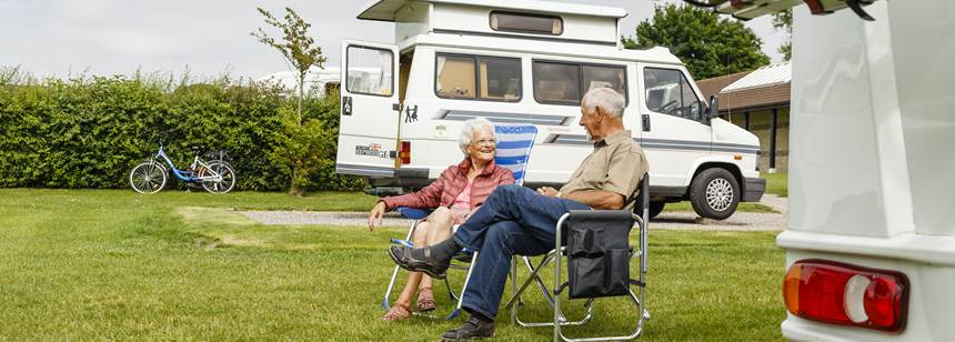 Couple sat outside campervan on Salisbury campsite