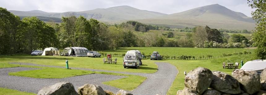 Grass and hardstanding pitches with views of the rolling hills of Cumbria