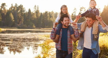 Happy family by a beautiful wood-surrounded lake